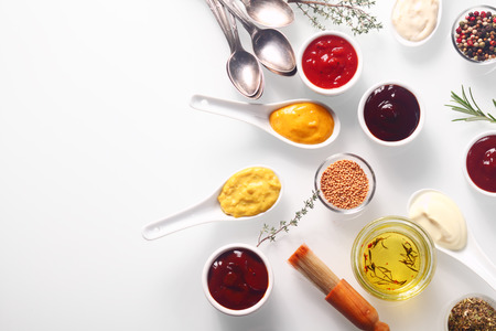 marinate: Close up Various Spicy Rubs and Marinades on White Table with Spoons and Brush, Emphasizing Copy Space. Stock Photo