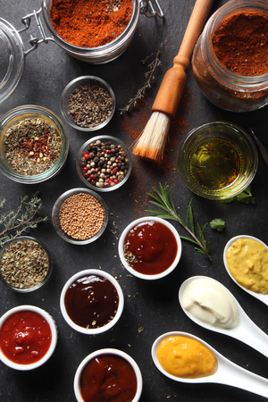 potherbs: Close up Assorted Seed Type Spices and Sauces on Containers Placed on Top of the slate Table Stock Photo