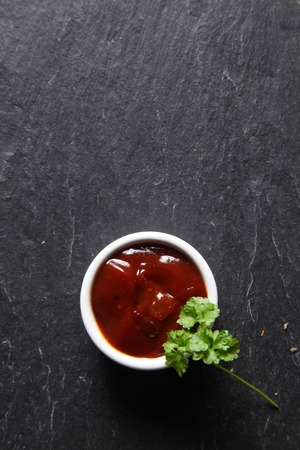 emphasizing: Close up Aerial Shot of Spicy Sauce with Green Leaves on slate Black Table, Emphasizing Copy Space.
