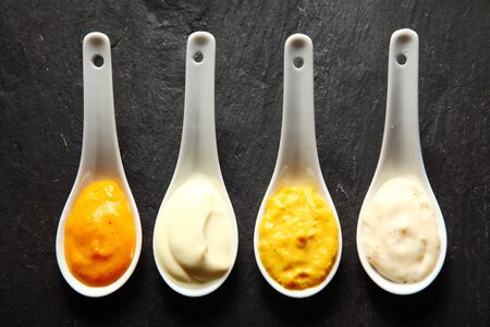 pastes: Close up Assorted Spicy Rub and Marinade Pastes on White Spoons Served on Top of slate plate Table. Stock Photo