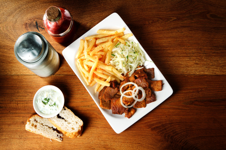 pub food: Gourmet Beef Steak, French Fries and Shredded Cabbage on Wooden Table with Bread and Sauce.