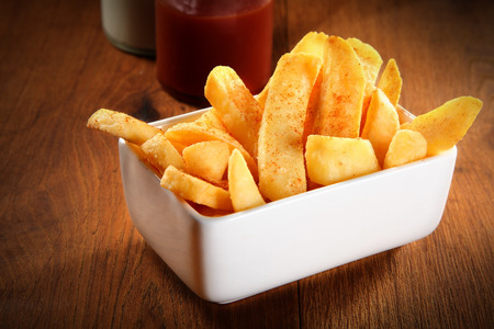 wedges: Close up Crispy Potato French Fries on White Plate on Wooden Table Stock Photo