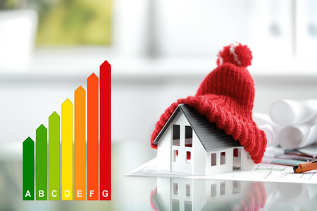 eficiencia: Concepto del rendimiento energético con la tabla de clasificación de la energía y una casa con bobble el sombrero rojo Foto de archivo