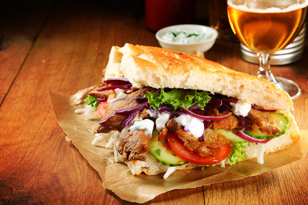 pita bread: Close up Burger Slice with Grilled Meat Doner and Veggies on Brown Paper, Placed on Wooden Table.