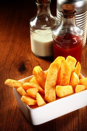 wedges: Close up French Fries on Wooden table with Ketchup and Salt on the Side