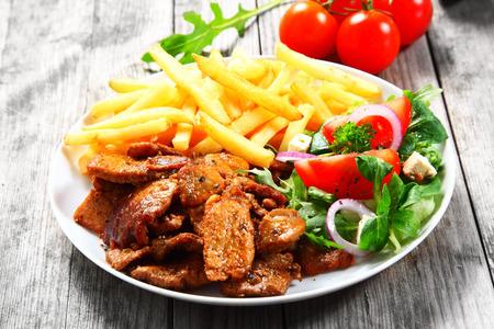 豚肉、野菜とフライド ポテト、役立った木製のテーブルの上に白いプレート上のおいしいグルメ健康を閉じます。