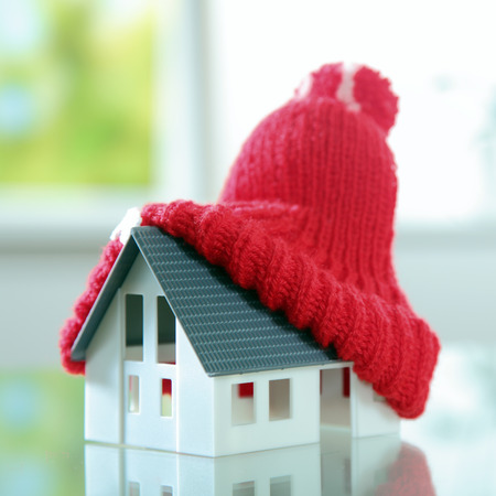 bobble: Close up Red Knitted bobble hat on Top of Cute Little House Placed on the Table.