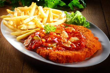schnitzel: Close up Saucy Crumbled Zigeunerschnitzel with Potato Fries on White Plate