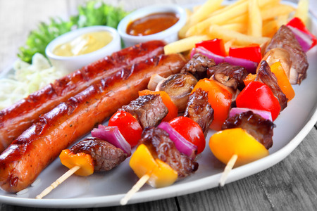 frites: Close up Gourmet Tasty Kebabs and Grilled Sausage on White Plate