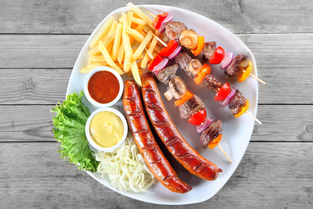 Close up Aerial Shot of Appetizing Kebabs, Sausage, Potato Fries and Veggies on Plate with Sauces. Placed on Wooden Table.
