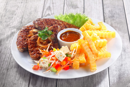 Close up Gourmet Fried Meat Slices with Potato Fries and Sauces on White Plate, Served on Wooden Table. Zdjęcie Seryjne