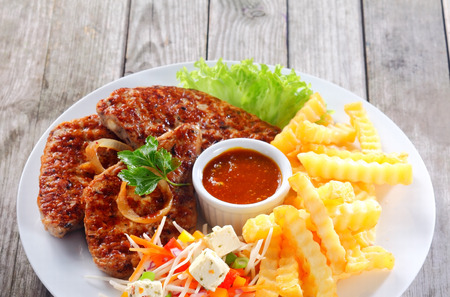 crinkle: Close up Appetizing Fried Escalope with Potato Fries on White Plate, Served on Wooden Table.