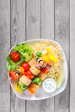 Close up Aerial Shot of Appetizing Kebabs on Flavored Yellow Rice with Veggies and Mustard Sauce, Served on Wooden Table with Copy Space. Stock fotó