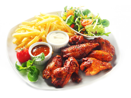 Close up Gourmet Fried Chicken with Potato Fries, Fresh Veggies and Sauces on White Plate. Isolated on White.