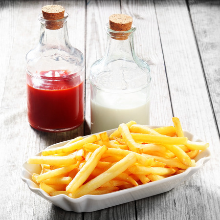 Close up Crispy Potato French Fries on White Plate with Sauces in Bottles on the Side, Placed on Wooden Table.
