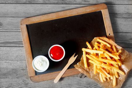 emphasizing: Close up Fried Potatoes Fries and Sauces Above Black Chalkboard with a Wooden Background, Emphasizing Copy Space.