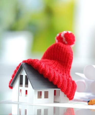 Energiebesparing Schot van Conceptuele Red gebreide muts bovenop Miniatuur Huis voor isolatie en isolatie concepten Stockfoto
