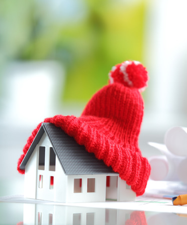 Energy saving Shot of Conceptual Red Knitted Hat on Top of Miniature House for isolation and insulation concepts photo