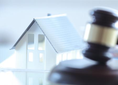 bienes raices: Close up Conceptual Casa miniatura blanco encima de la mesa, junto Mazo de la corte.