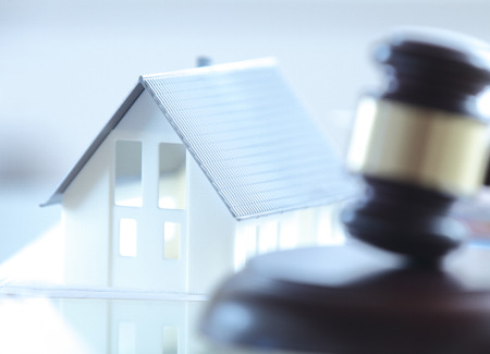 law: Close up Conceptual White Miniature House on Top of the Table Beside Court Gavel.