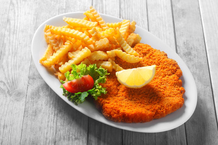 nosh: Close up Tasty Recipe of Crumbled Escalope with Potato Fries, Styled with Slice of Lemon and Tomato and Lettuce. Stock Photo