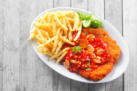 schnitzel: Close up Gourmet Potato Fries and Saucy Escalope on White Plate, Served on Wooden Table.