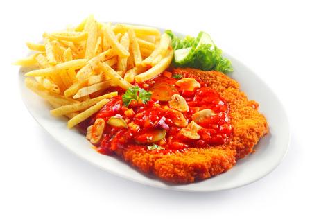 Close-up Smakelijke Combinatie van Afgebrokkelde dunne vlees en frietjes met groenten op witte plaat, geïsoleerd op wit.