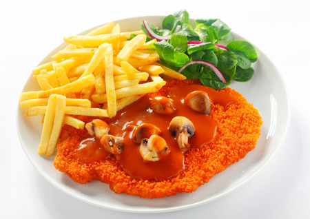 schnitzel: Close up Fried Crumbed Escalope with French fries on White Plate. Isolated on White.