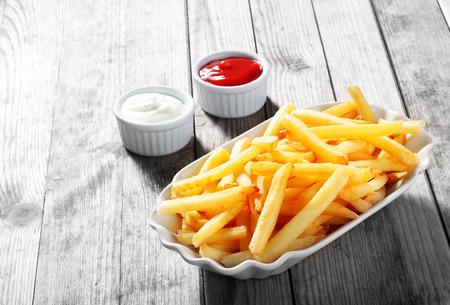 Close-up Knapperige frietjes op wit bord met twee dipsaus, geserveerd op rustieke houten tafel Stockfoto - 36832704