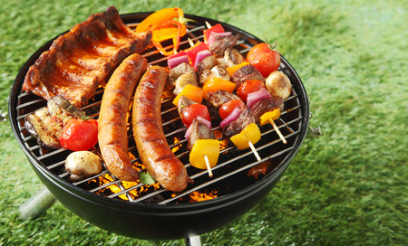 meat on grill: Selection of meat grilling over the coals on a portable barbecue with spicy sausages, beef kebabs and racks of ribs, outdoors on green grass with copyspace