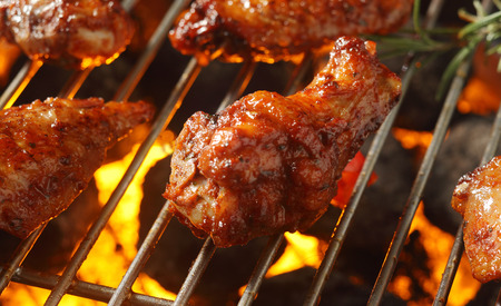 Spicy marinated chicken drumsticks cooking over the flames of a barbecue crispy the skin for a delicious summer picnic Banco de Imagens