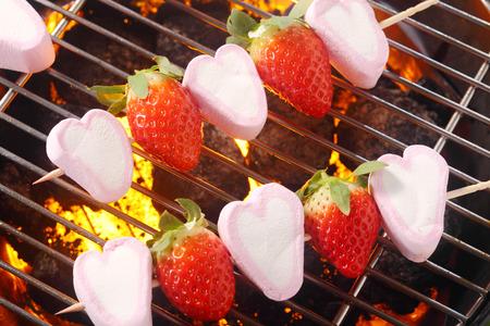 Postre de verano con malvavisco y fresas rosca en los pinchos para asar sobre las brasas de una barbacoa para un convite de picnic