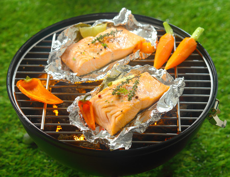 Grilled salmon steaks with baby vegetables cooking on tin foil over a barbecue outdoors in summer with baby carrots and sweet pepper Banco de Imagens
