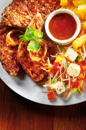 Close up Gourmet Fried Marinated Meat with Tomato Sauce and Cheese Paired with Potato Fries photo