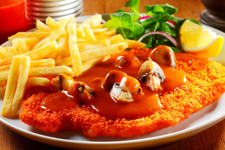 Close up Appetizing German Cuisine - Gourmet Jägerschnitzel with Sauce and Crispy Potato Fries on White Plate with Herbs and Lemon.