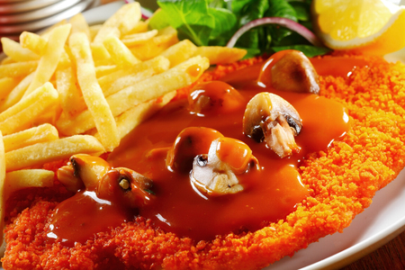 schnitzel: Close up Tasty Gravy on Crispy Escalope with Mushrooms Paired with Potato Fries