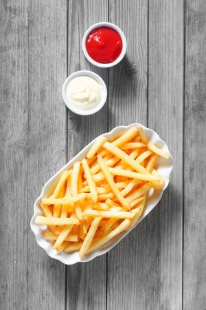 mayonesa: Cierre de tiro aéreo de las patatas fritas saladas con salsas en el lado en la cima de la tabla de madera.