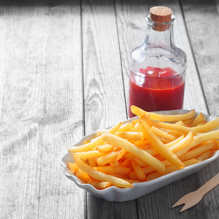 quick snack: Close up Potato French Fries on White Plate and Tomato Sauce in Glass Jar on Top of Wooden Table