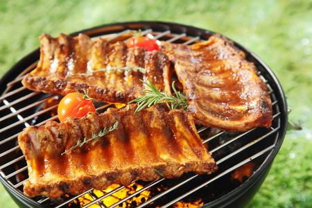 Sappige pittige spareribs op een barbecue grillen boven de hete kolen met verse rozemarijn en tijm en cherry tomaten, buiten op gras