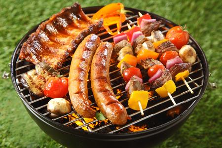 barbecue: Surtido de carne a la parrilla en una barbacoa de verano con salchichas, costillas picantes y los pinchos de carne con verduras, al aire libre en un c�sped verde