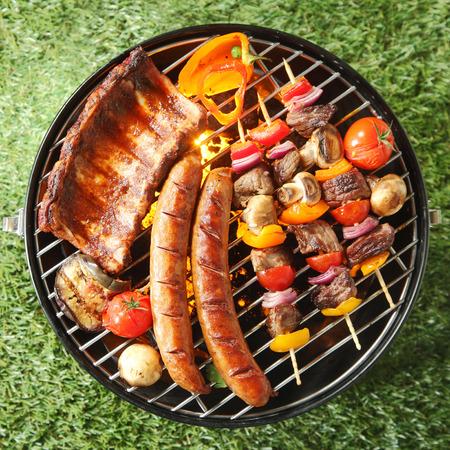 barbecue: Sabroso surtido de carne en una barbacoa de verano con salchichas, brochetas de carne y costillas de cerdo con tomate y champi�ones, vista a�rea sobre la hierba verde