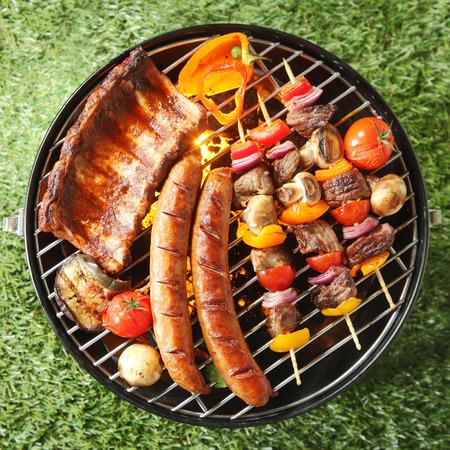 cookout: Tasty assortment of meat on a summer barbecue with sausages, beef kebabs and spare ribs with tomatoes and mushrooms, overhead view over green grass