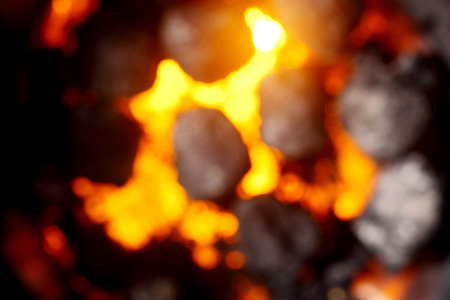 briquettes: Blurred background of hot glowing coals and charcoal in a fire or on a portable barbecue, full frame