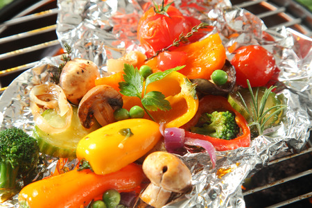 vegetable tin: Colorful selection of fresh roasted vegetables grilling over a barbecue fire on aluminum foil for a healthy vegetarian or vegan picnic or as an accompaniment