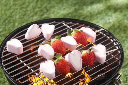 Fun dessert of ripe strawberries and heart shaped marshmallows grilling over a barbecue in spring for a romantic Valentines picnic photo