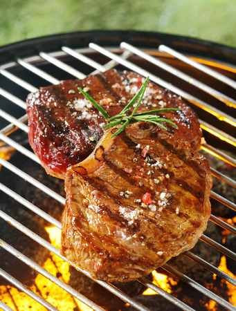 coals: Tender juicy beef steaks grilling over the flames on a portable summer barbecue outdoors on a green grassy lawn