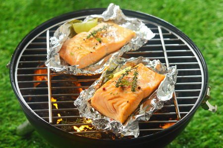Two gourmet salmon cutlets seasoned with fresh herbs grilling on a fire in a portable barbecue outdoors on grass ready to be served with lemon photo