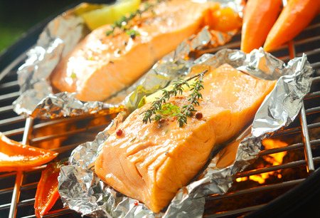 green fish: Fresh succulent marine salmon steaks flavored with sprigs of thyme grilling over a barbecue on aluminum foil with sweet pepper and baby carrots