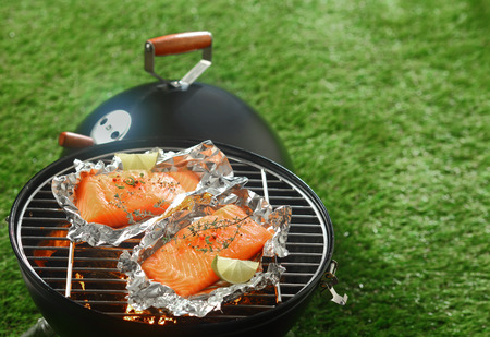 Gourmet summer barbecue with grilled salmon fillets cooking over the fire in tin foil wrappers ready to be served with lemon garnish, outdoors on green grass with copyspace