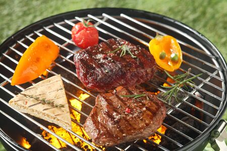 barbecue: Succulent tender rump steak seasoned with fresh rosemary grilling on a barbecue with a slice of pita bread, tomato and sweet peppers